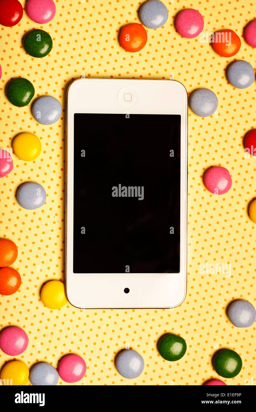 colorful candies and smartphone - Stock Image