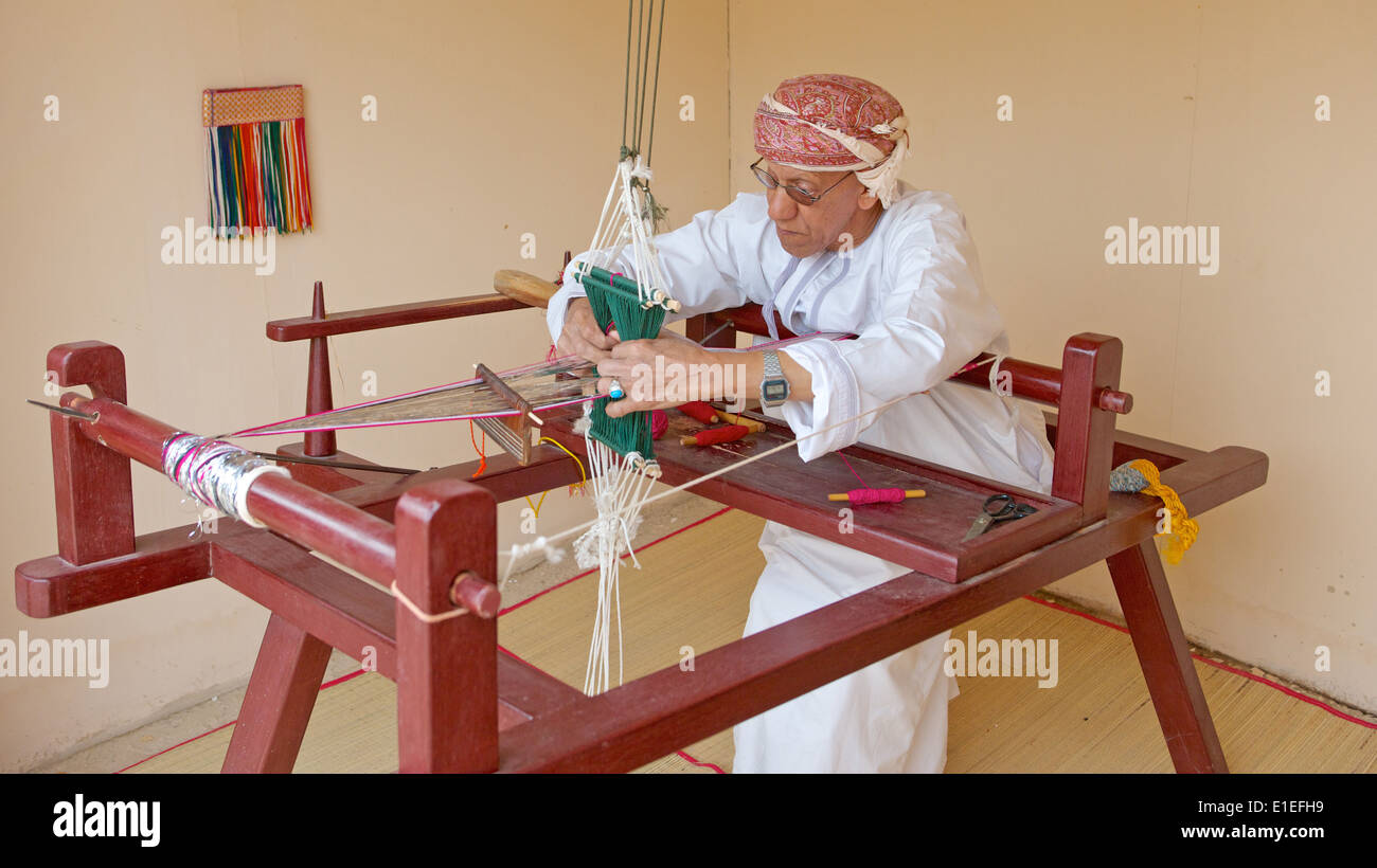An Omani weaver, wearing a traditional muzzar (headcloth), at work in Muscat, in the Sultanate of Oman. Stock Photo