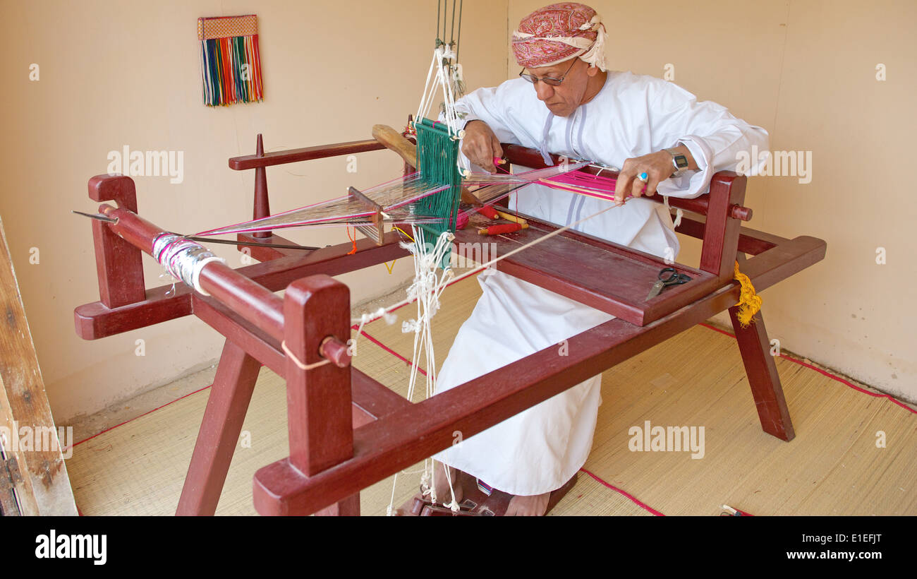 An Omani weaver, wearing a traditional muzzar (headcloth), at work in Muscat, in the Sultanate of Oman. - Stock Image