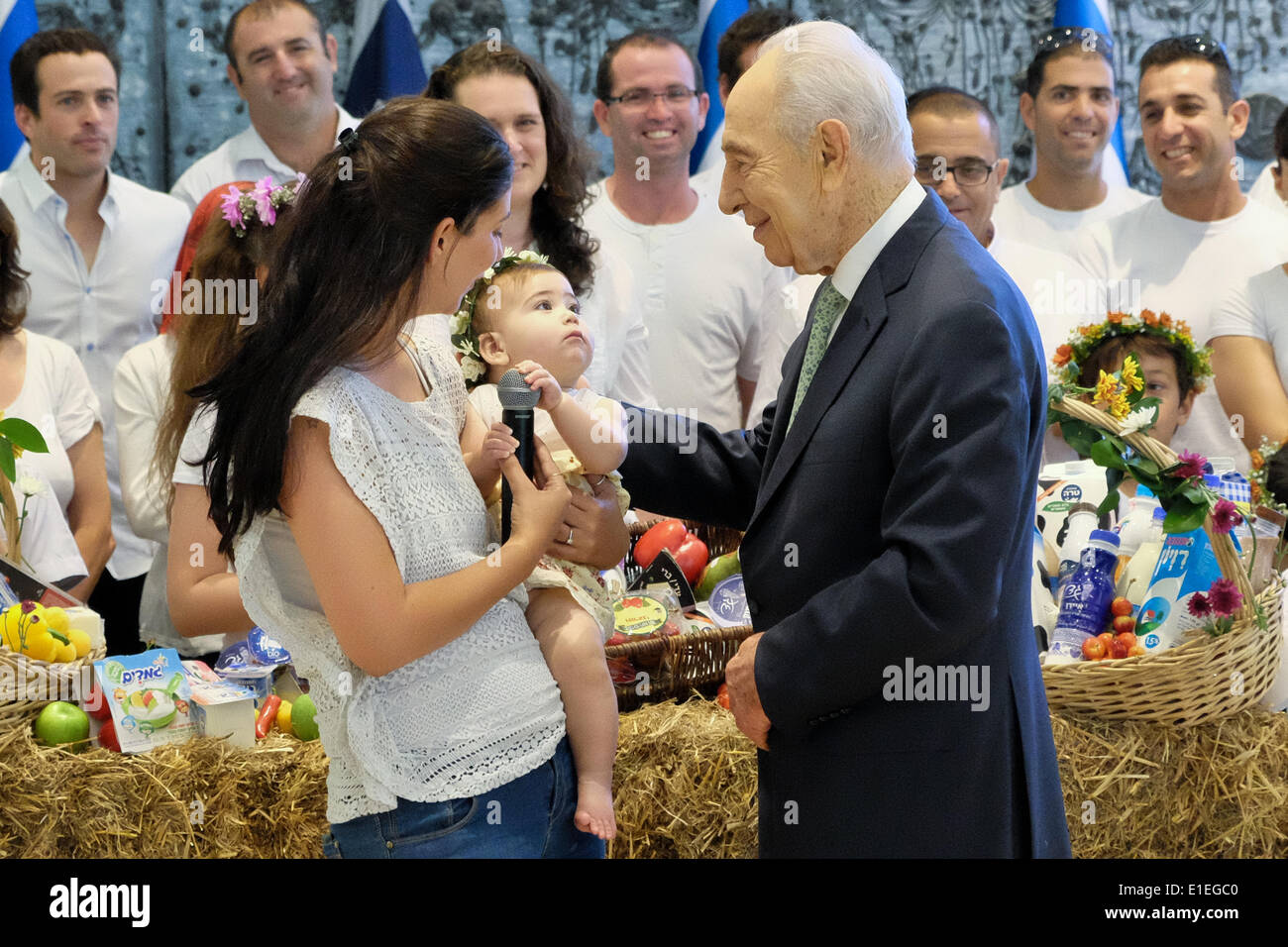 Jerusalem, Israel. 02nd June, 2014. Israeli President SHIMON PERES is presented with a newborn infant in the custom of the kibbutz. The President hosted a Bikkurim Festival for the Shavuot holiday, celebrating the giving of the Torah at Mt. Sinai. Also referred to as the Harvest Festival, in ancient times Jewish farmers brought their first fruits of the season to the Temple in Jerusalem as offerings. Credit:  Nir Alon/Alamy Live News - Stock Image