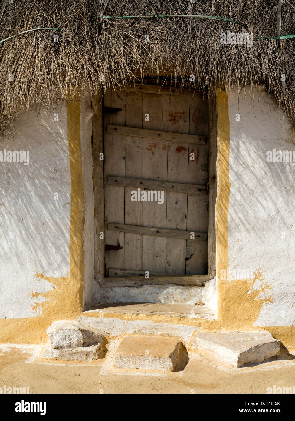 India, Rajasthan, Jaisalmer, door of thatched Guest House of Thar Desert farm, with painted walls outside main compound - Stock Image