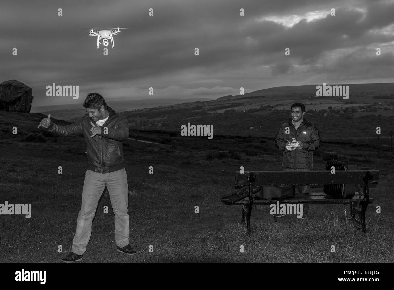 Diversity: Two Asian men socialising - enjoying flying a radio control helicopter with video camera drone, Yorkshire, UK - Stock Image