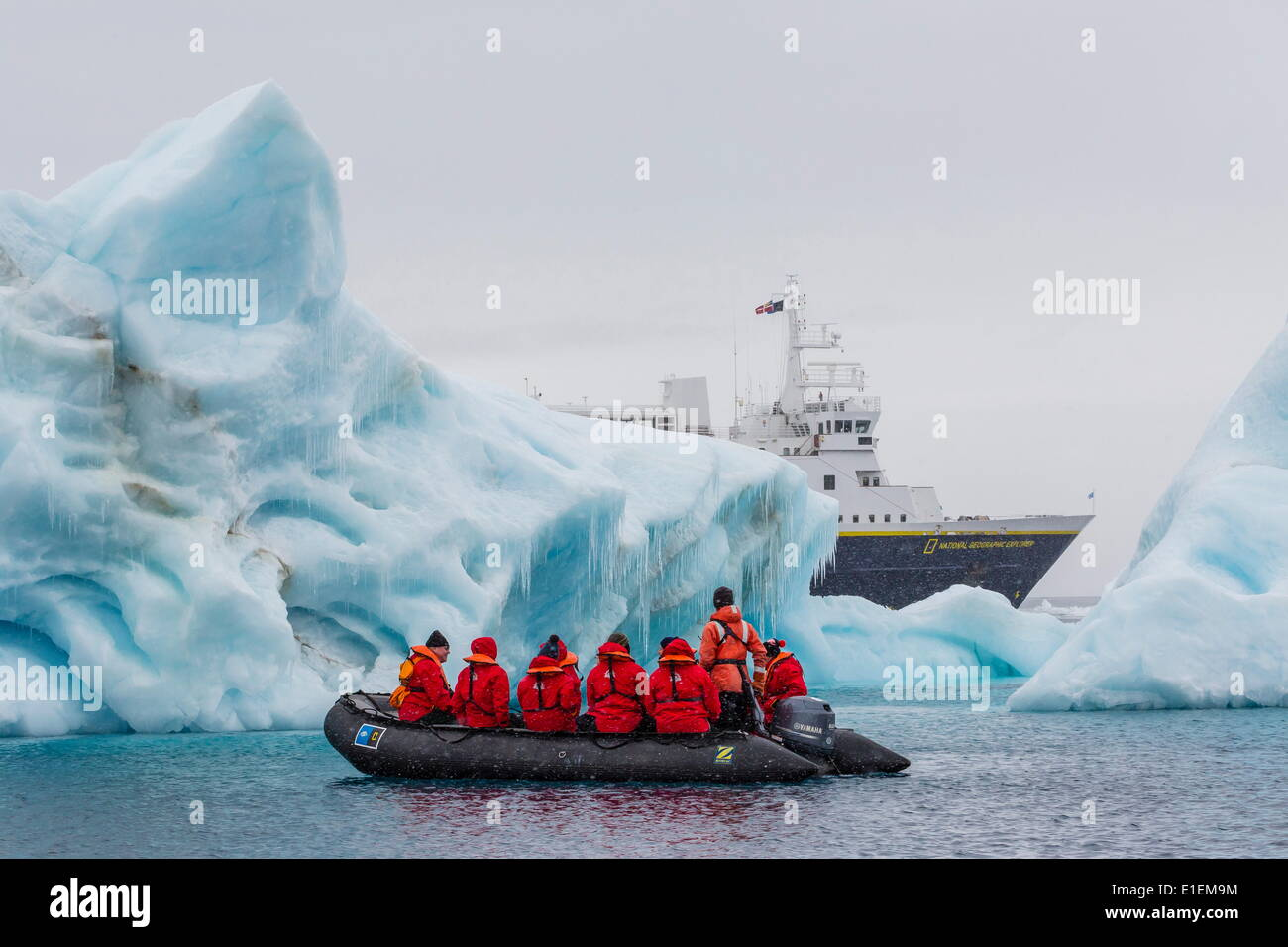Lindblad Expeditions guests in a Zodiac approach a glacial iceberg at Brown Bluff, Weddell Sea, Antarctica, Polar Regions - Stock Image