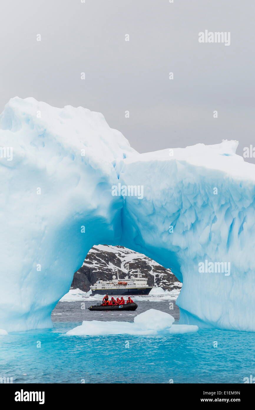 Lindblad Expeditions guests in a Zodiac as seen through an arch in an iceberg at Cierva Cove, Antarctica, Polar Regions - Stock Image