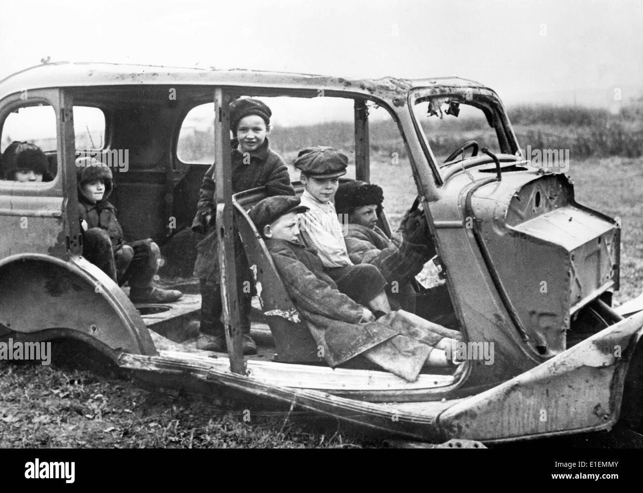 The Nazi news image shows local children playing in the wreck of a car in the German occupied areas along the Eastern Stock Photo