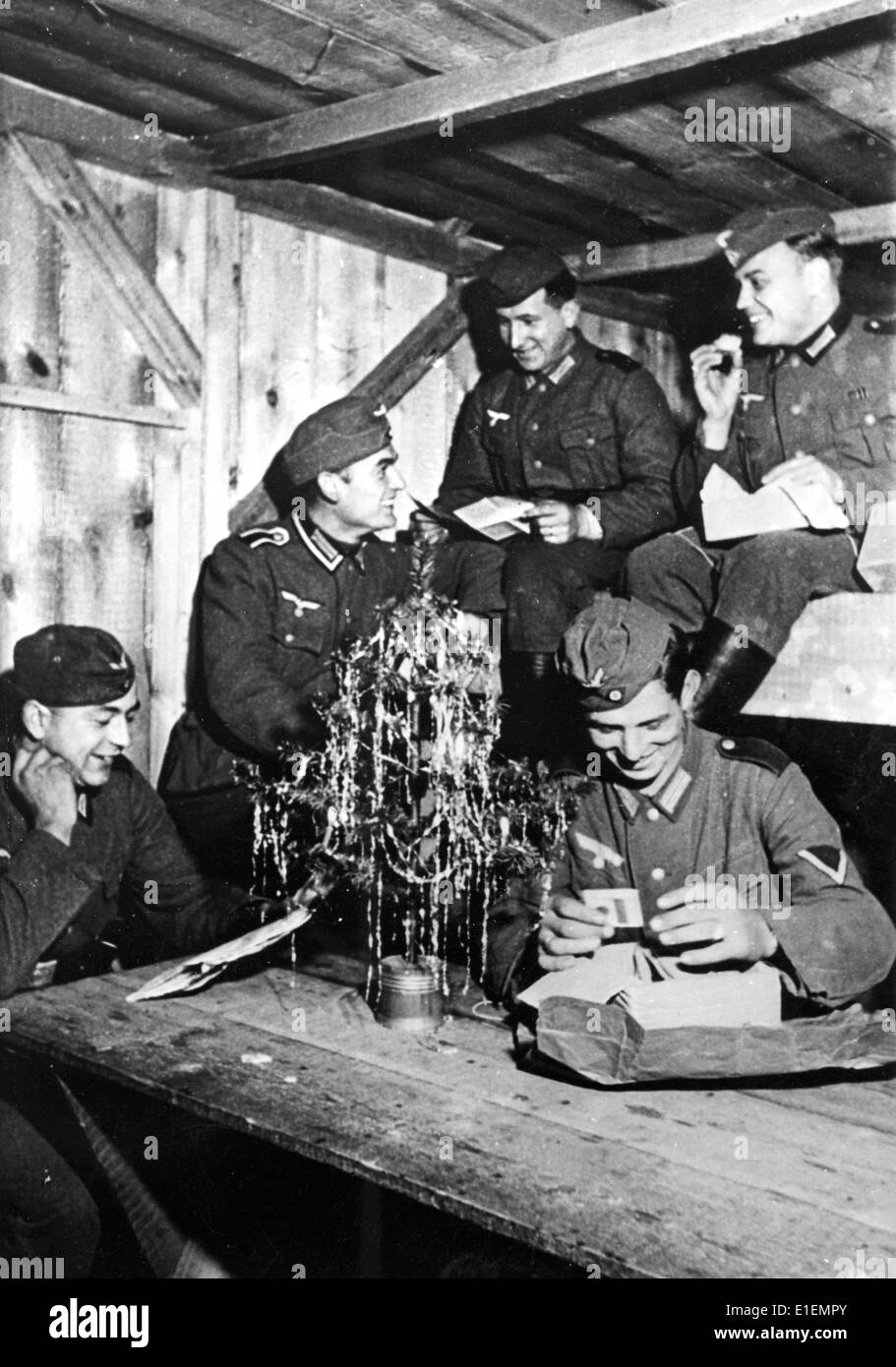 Soldiers of the German Wehrmacht read letters on Christmas in a wooden house at the Eastern Front, published 24 Stock Photo