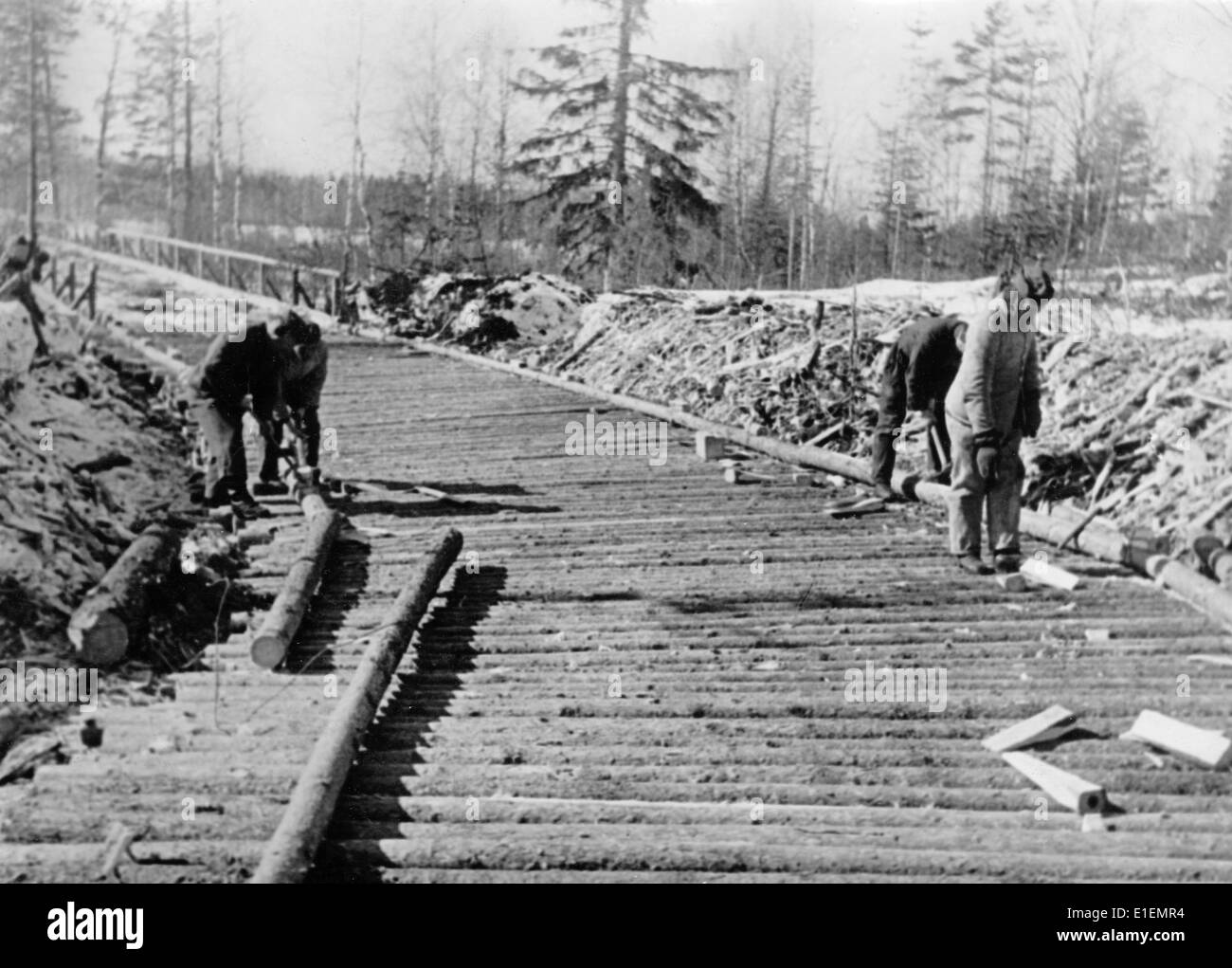 Propaganda text! from Nazi news reporting on the back of the picture: 'Corduroy roads over muddy roads. In the first Stock Photo