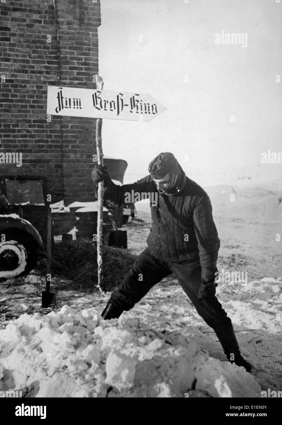 A soldier puts up a signpost showing the way to a front cinema at the Eastern Front, published 02 March 1942. Propaganda Stock Photo