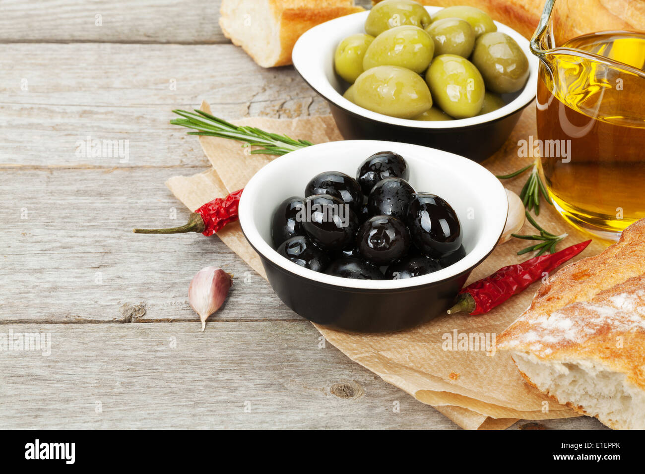 Italian food appetizer of olives, bread and spices on wooden table background with copy space - Stock Image