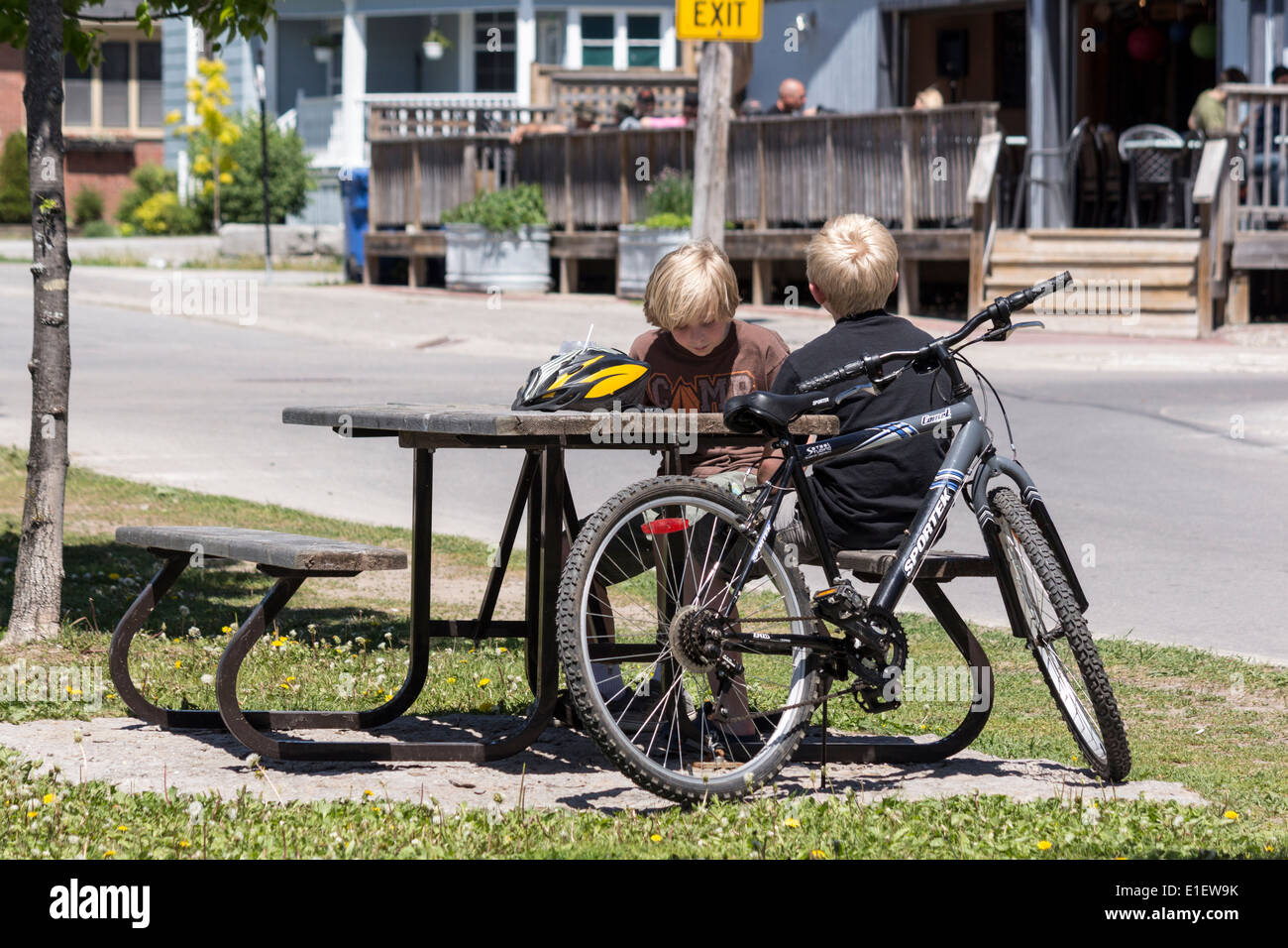 Two blond adolescent boys sitting on a picnic table with bike and helmet - Stock Image