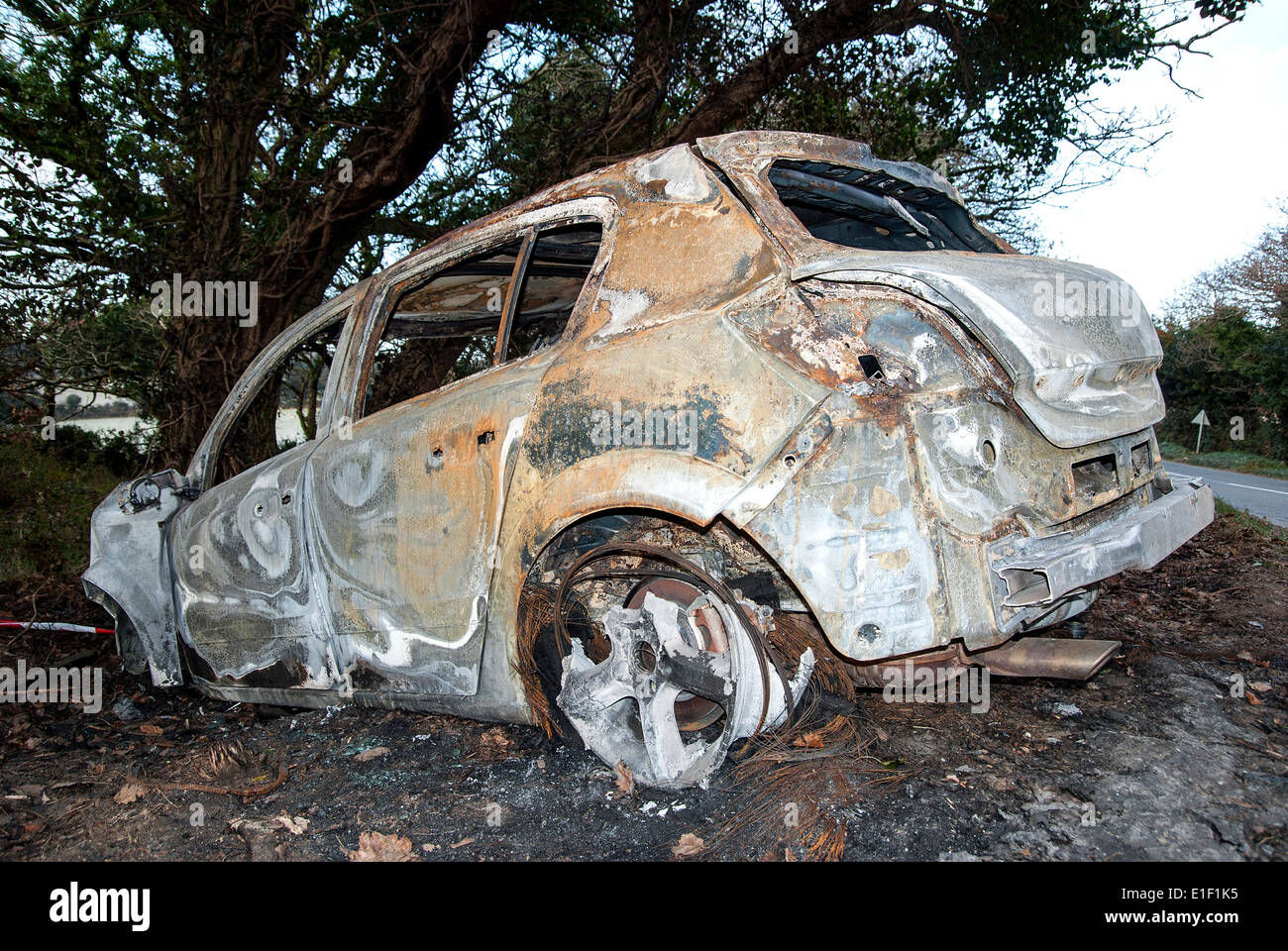 a crashed and burnt out car - Stock Image