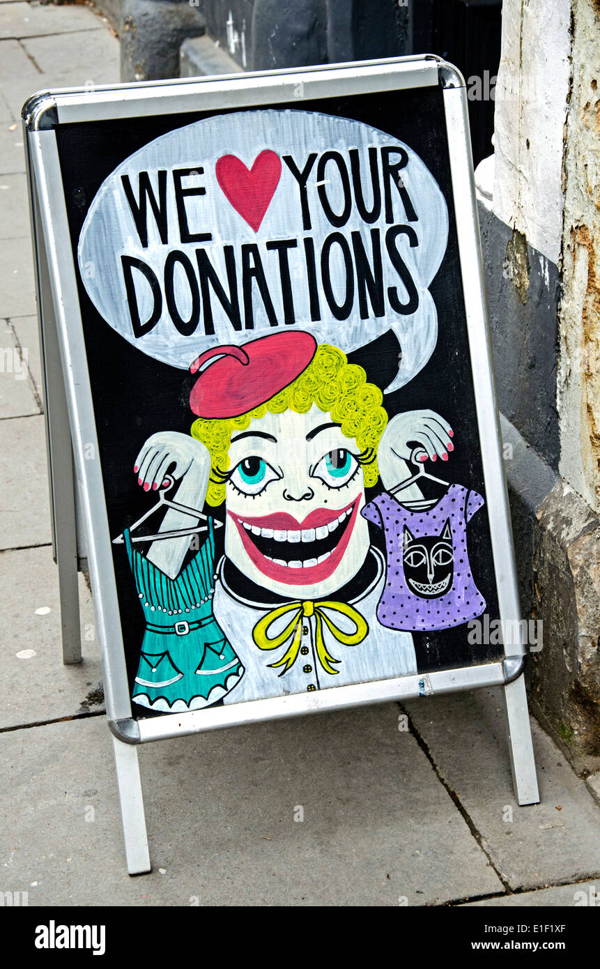 A-board outside a charity shop asking the public for donations of clothes. - Stock Image
