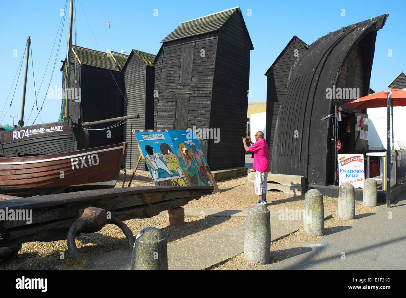 Visitor taking snapshot of girl looking through cartoon body picture board by the traditional black Net Huts, Hastings Old Town - Stock Image