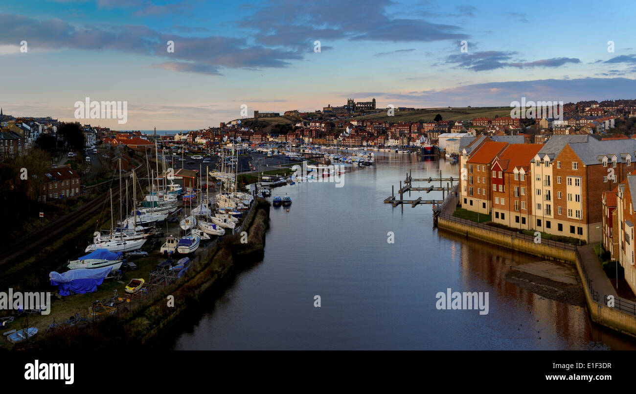 The river Esk flowing through the town of Whitby, overlooked by the ruined abbey. Whitby, North Yorkshire. March. - Stock Image