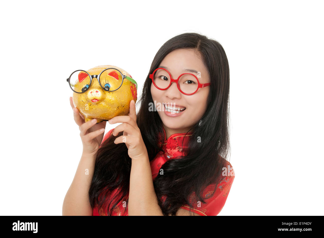 Beautiful Chinese woman wearing a traditional dress known as a Chipao holding a piggy bank Stock Photo