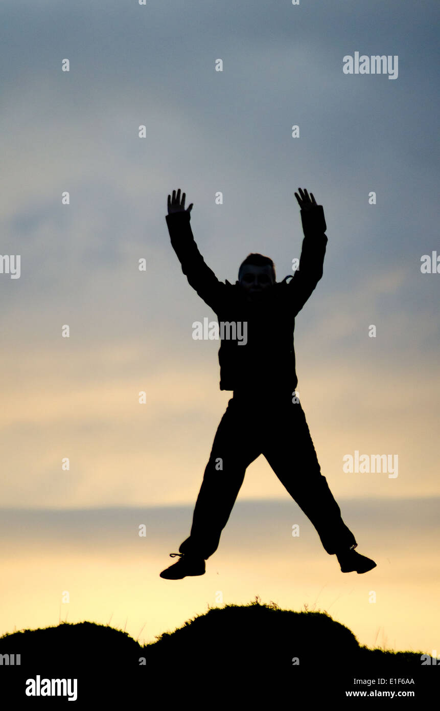 Silhouette of a boy jumping - Stock Image