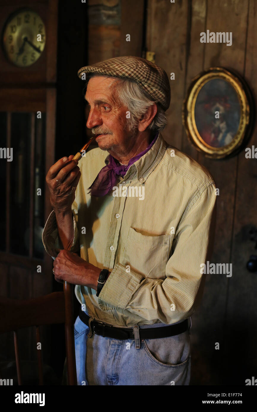 Artist Lowell Davis, smoking a pipe in his home at Red Oak II in Carthage, Missouri. - Stock Image