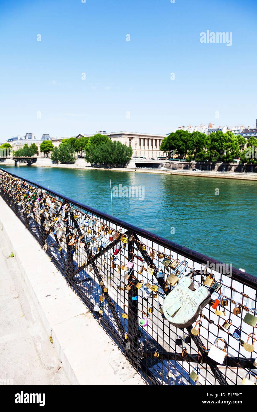 Love locks padlocks on fence overlooking the river Seine Paris France - Stock Image