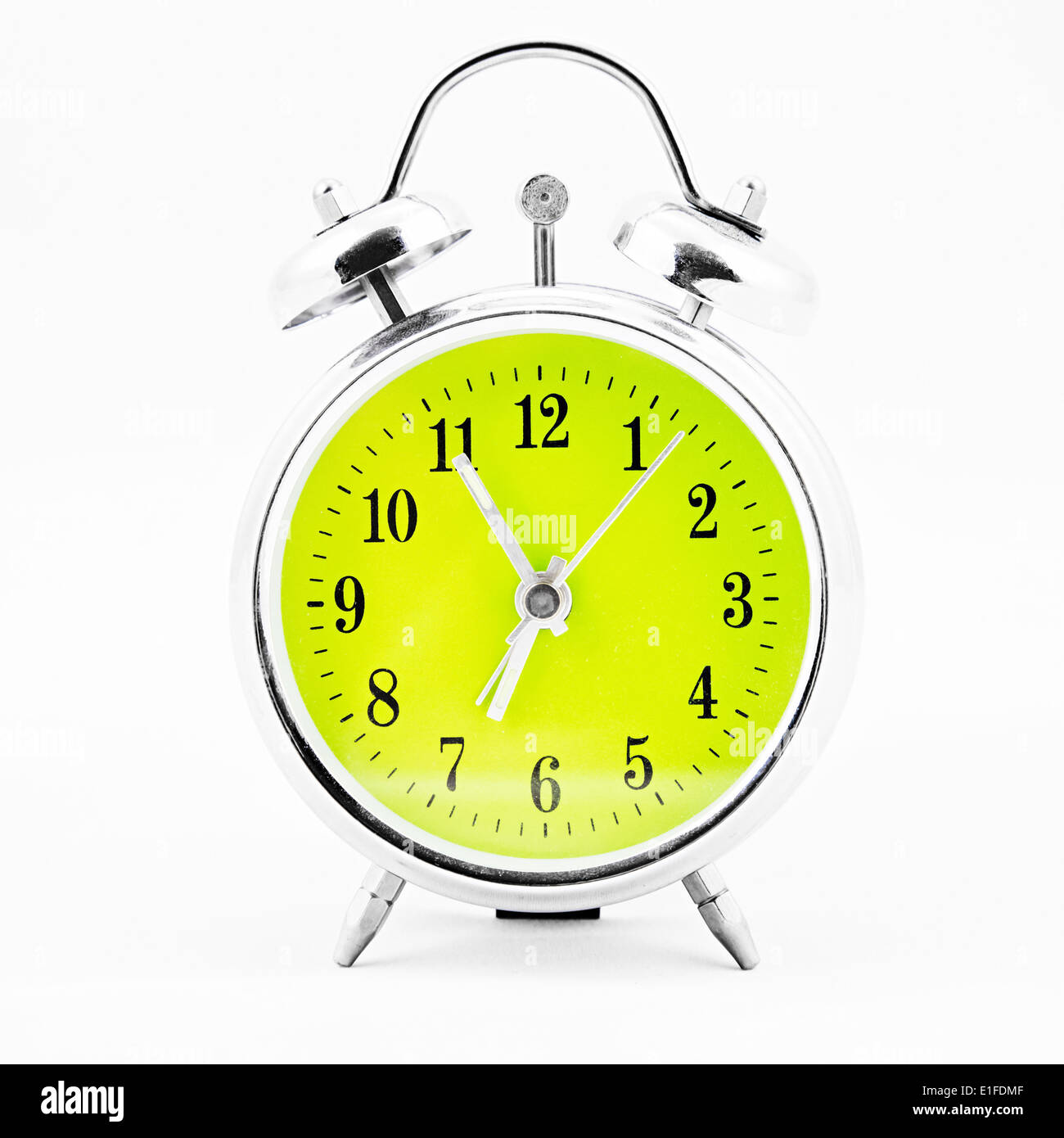 alarm clock on white background showing time five minutes before seven