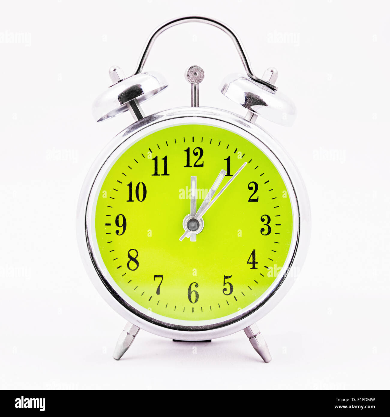 Alarm clock on white background. Showing time five minutes past twelve - Stock Image