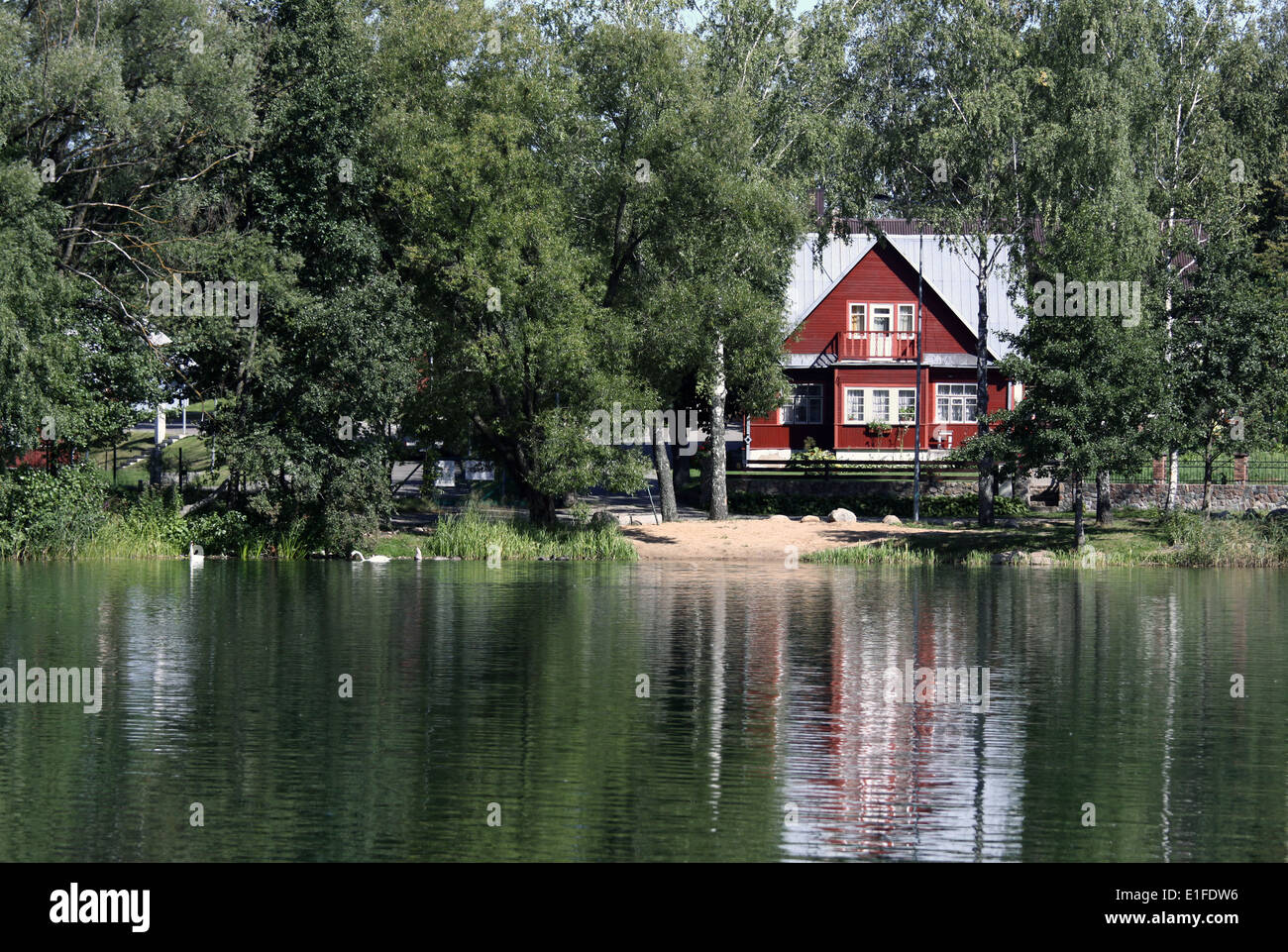 Remote summerhouse with reflection on the lake - Stock Image