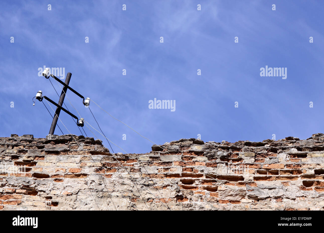 Collapsing telephone pole on the brick wall with plenty of copy space - Stock Image