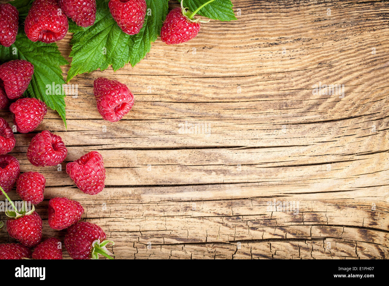 Raspberries on wooden table background. Copy space. Top view - Stock Image
