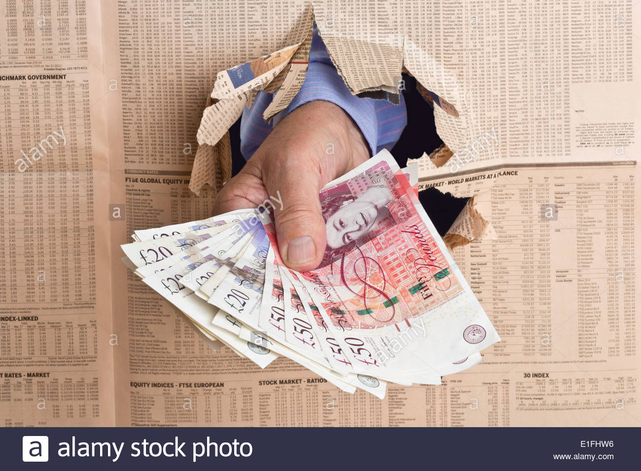 Mans hand holding sterling banknotes being thrust through a financial newspaper. - Stock Image