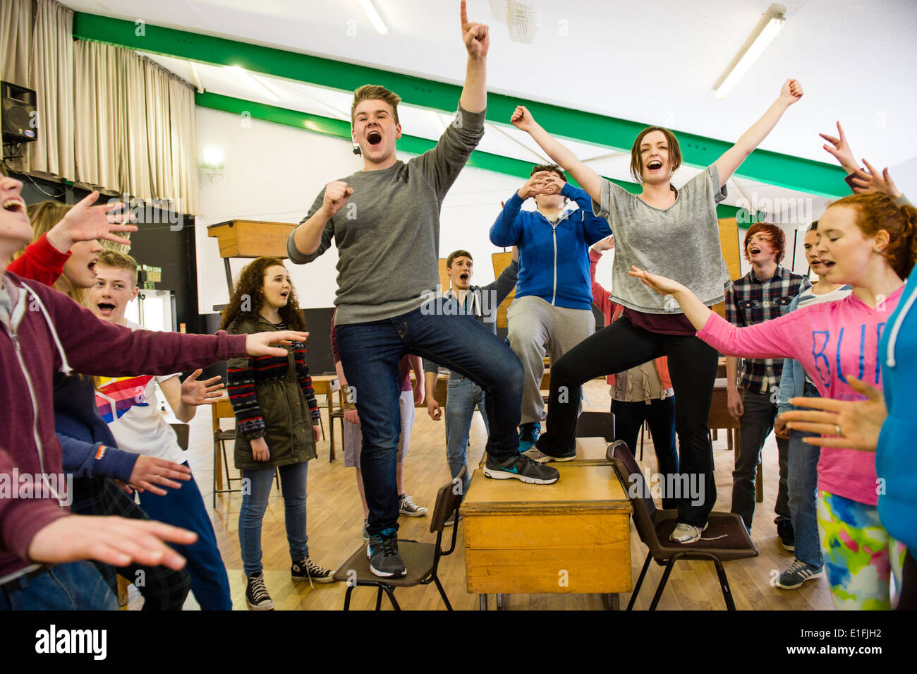 A group of teenagers in youth theatre rehearsing singing and acting for a musical theater performance, UK - Stock Image