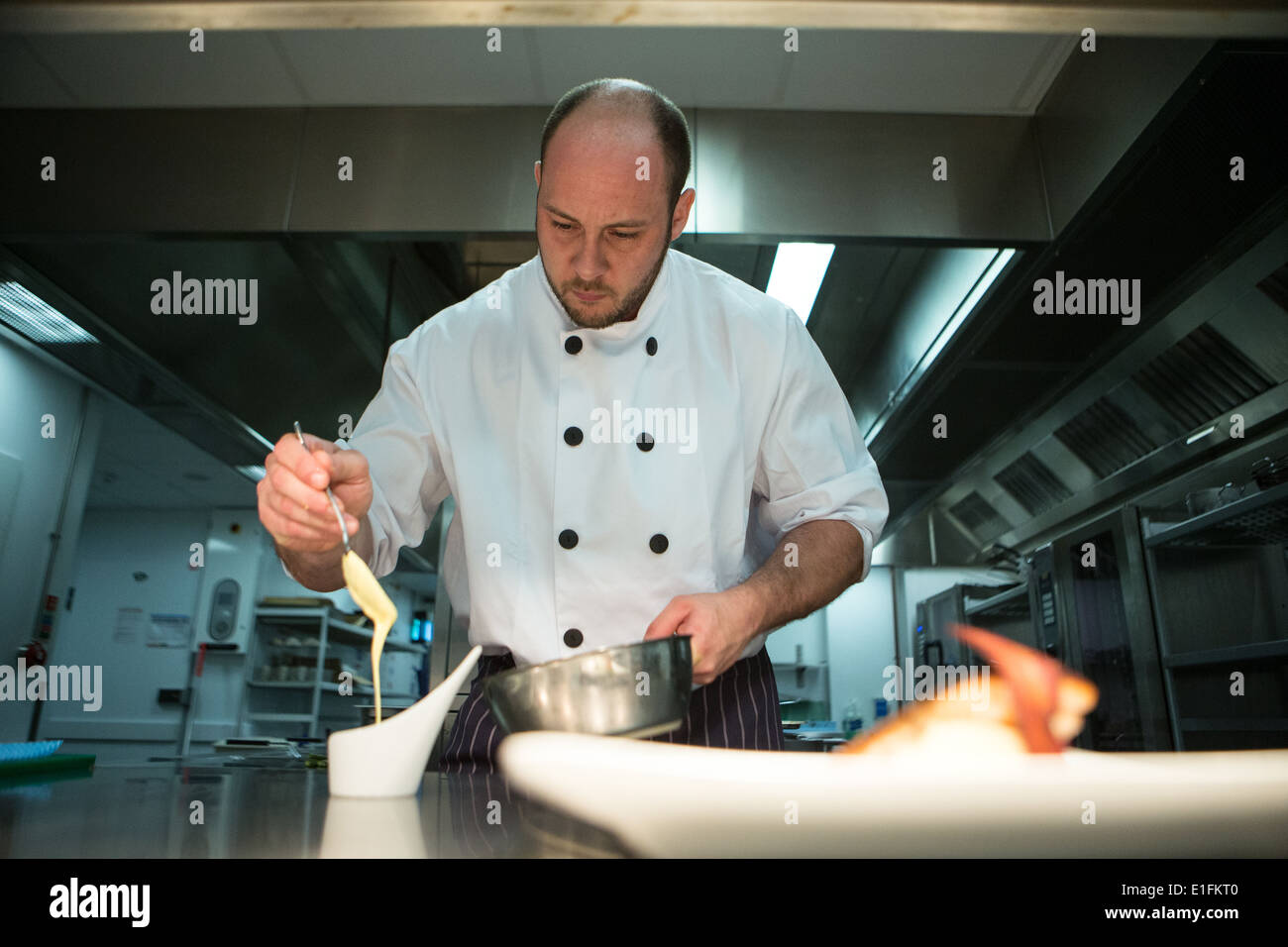 Chef in kitchen preparing a meal cooking pouring sauce Stock Photo ...