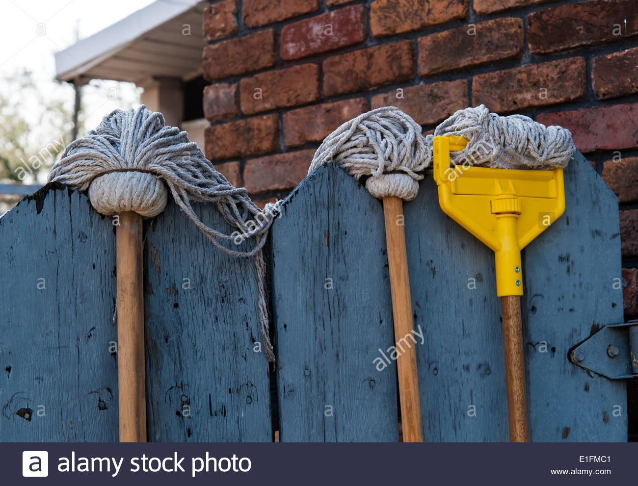 Several floor mop hanging to dry over a door - Stock Image