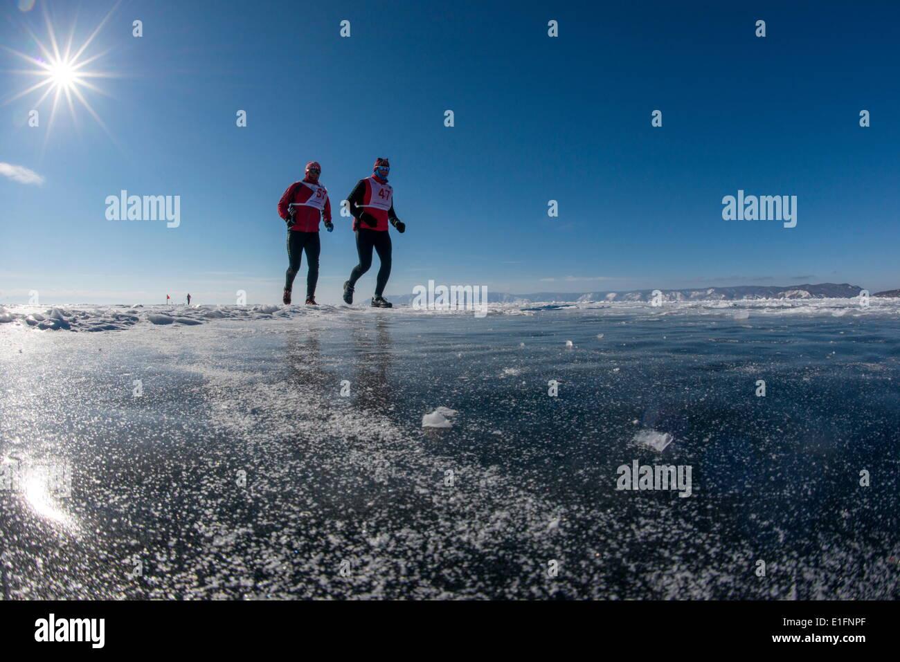 Runners in the 10th Baikal Ice Marathon, run on the frozen surface of the world's largest lake, Siberia, Irkutsk Oblast, Russia - Stock Image