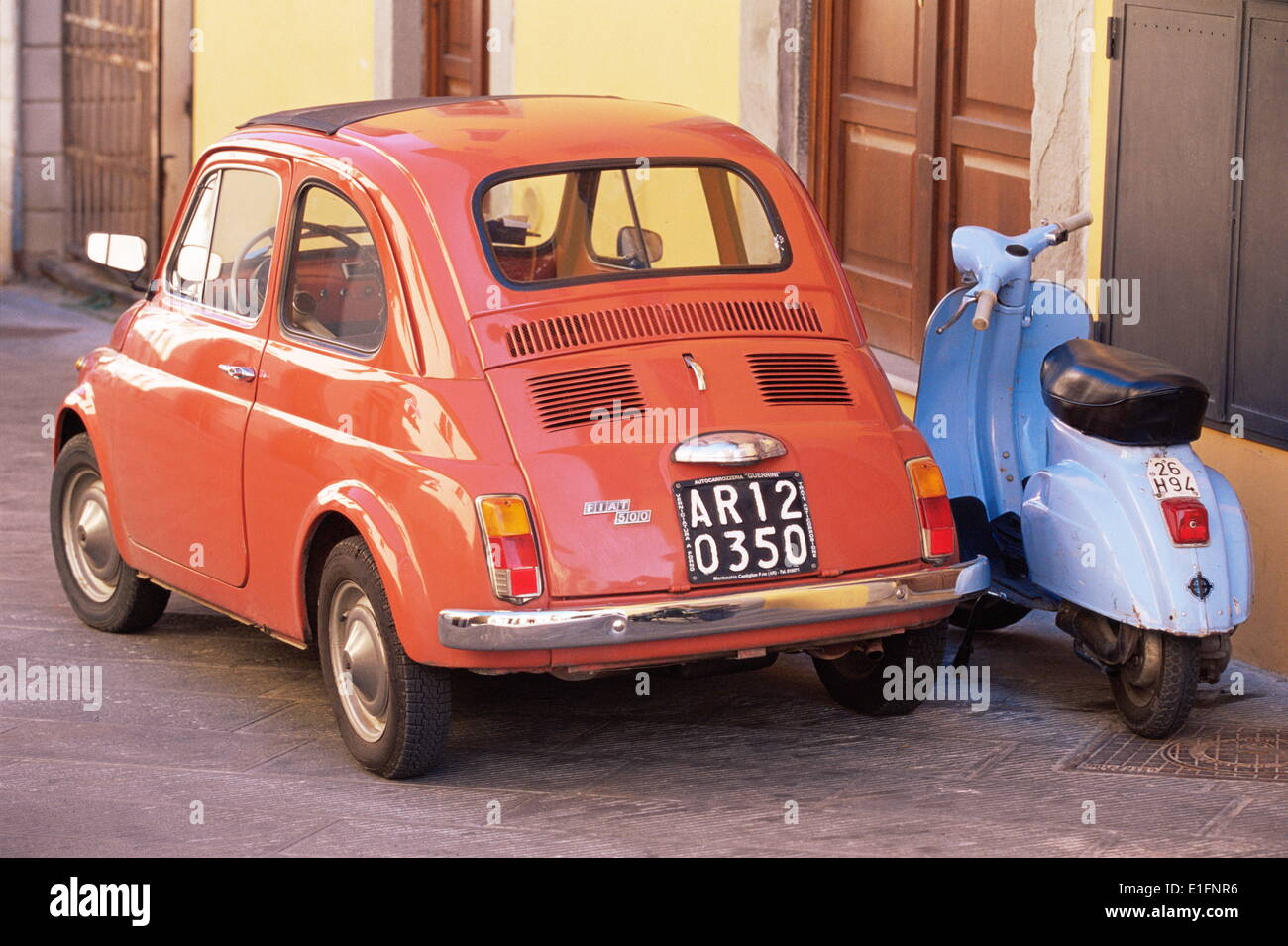 Fiat 500 Car And Old Blue Scooter Parked Together In Back Street
