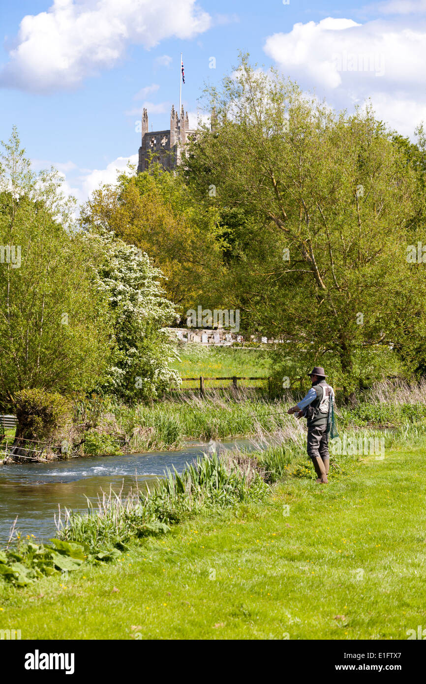 Fly fishing for trout on the River Coln opposite St Marys church in the Cotswold town of Fairford, Gloucestershire UK - Stock Image