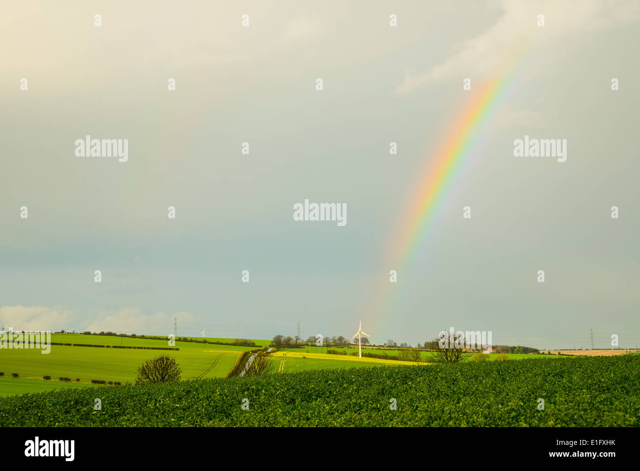 Rainbow and wind turbine near North Newbald in the Yorkshire Wolds - Stock Image