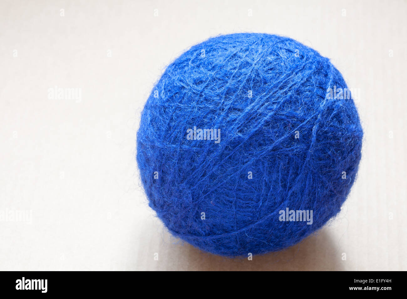 blue wool yarn skein on cardboard background - Stock Image