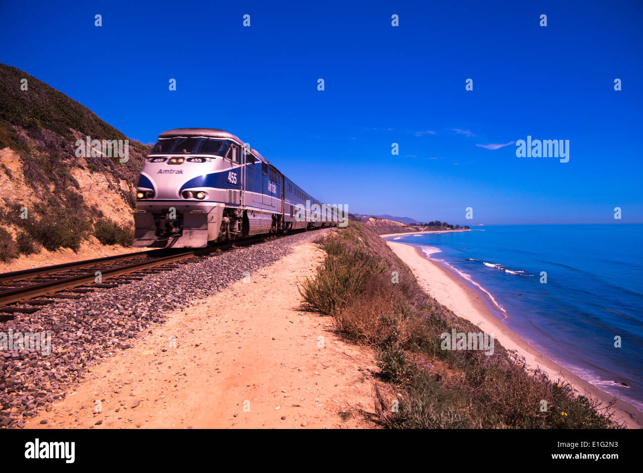 Surfliner express passenger train runs on tracks along Pacific Ocean near Rincon Beach; Central California, California, USA - Stock Image