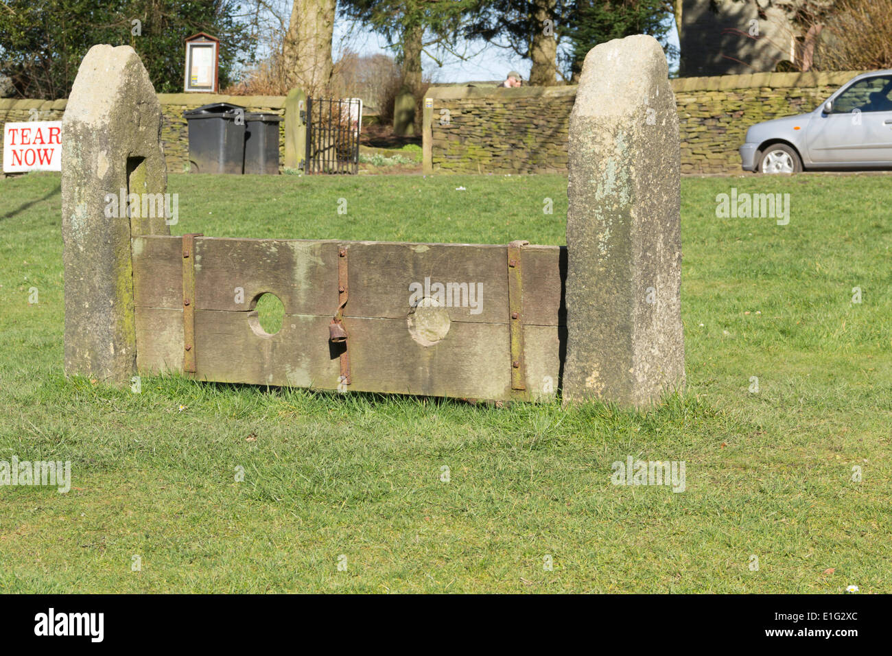 Punishment stocks on the village green in Rivington, Lancashire with the Unitarian chapel in the background. - Stock Image