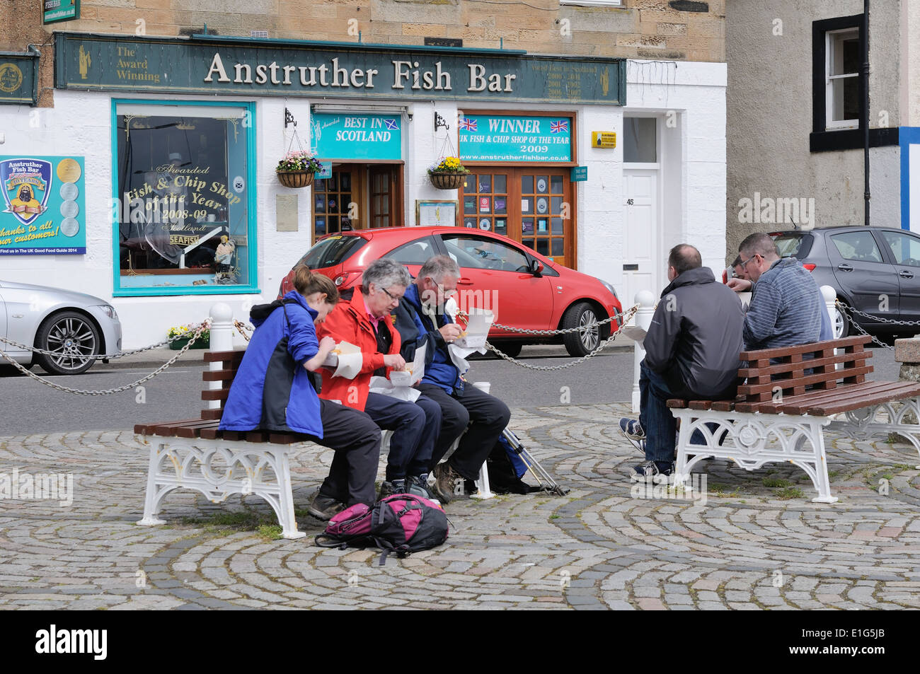 People eating fish and chips bought from the award winning Anstruther fish bar - Stock Image
