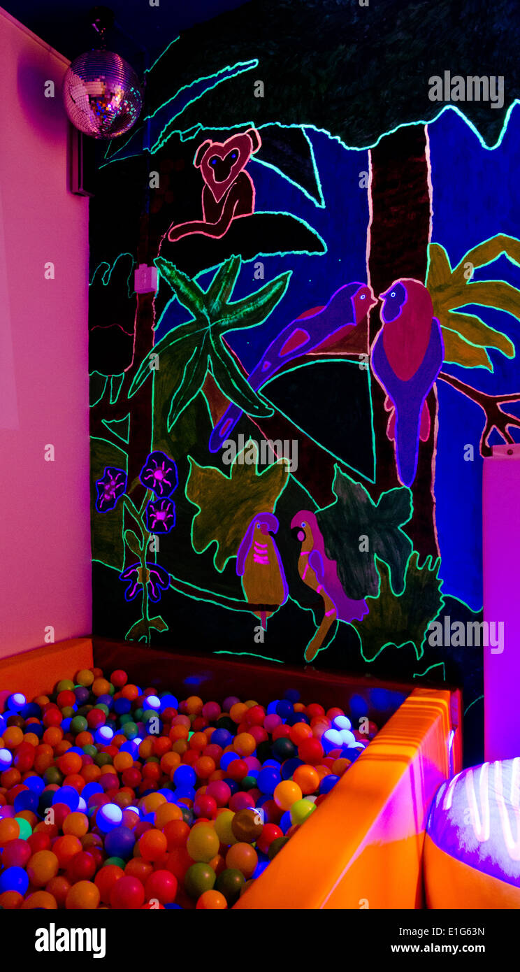 Adult ball pit and UV painted artwork in a disability charity's sensory room - Stock Image