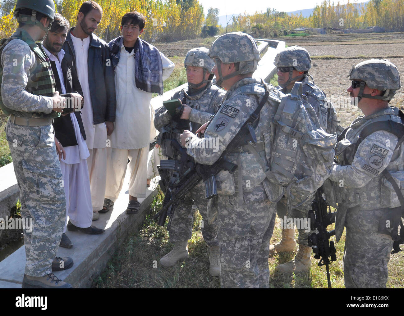 U.S. Soldiers and Sailors with the Nuristan Provincial Reconstruction Team (PRT) inspect a canal in Nalangar village in the Nur - Stock Image