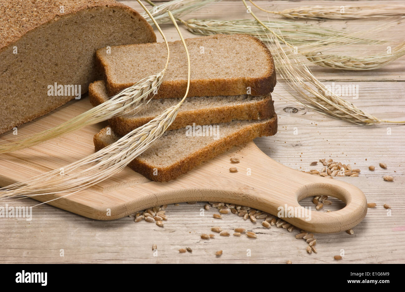 slices of rye bread and ears of corn on the wooden table - Stock Image