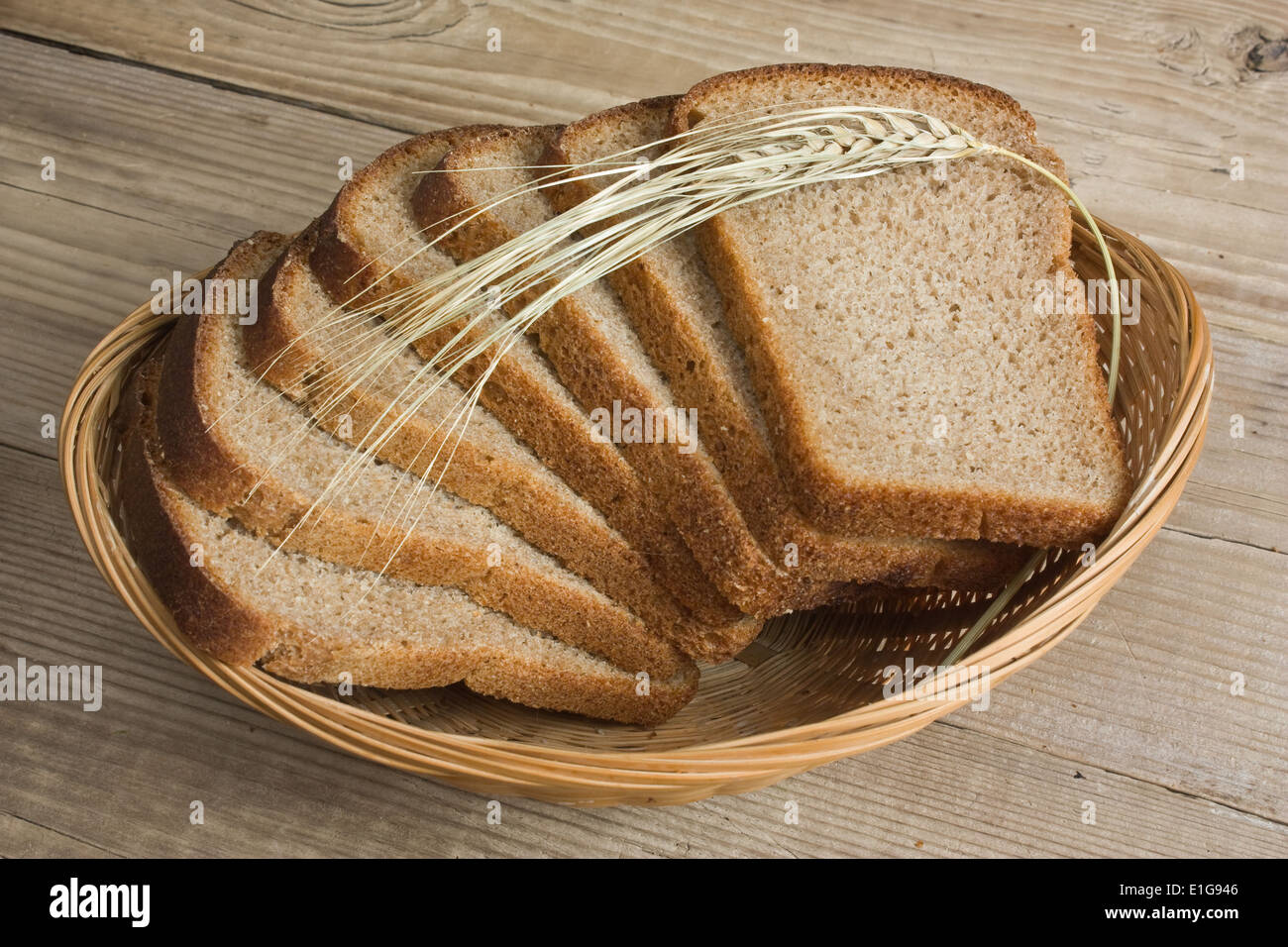 slices of rye bread and ears of corn in the basket - Stock Image