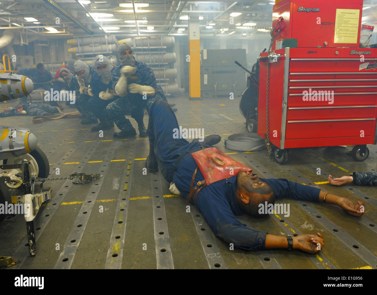 U.S. Sailors act as casualties of a simulated explosion aboard the aircraft carrier USS Abraham Lincoln (CVN 72) as a fire team - Stock Image