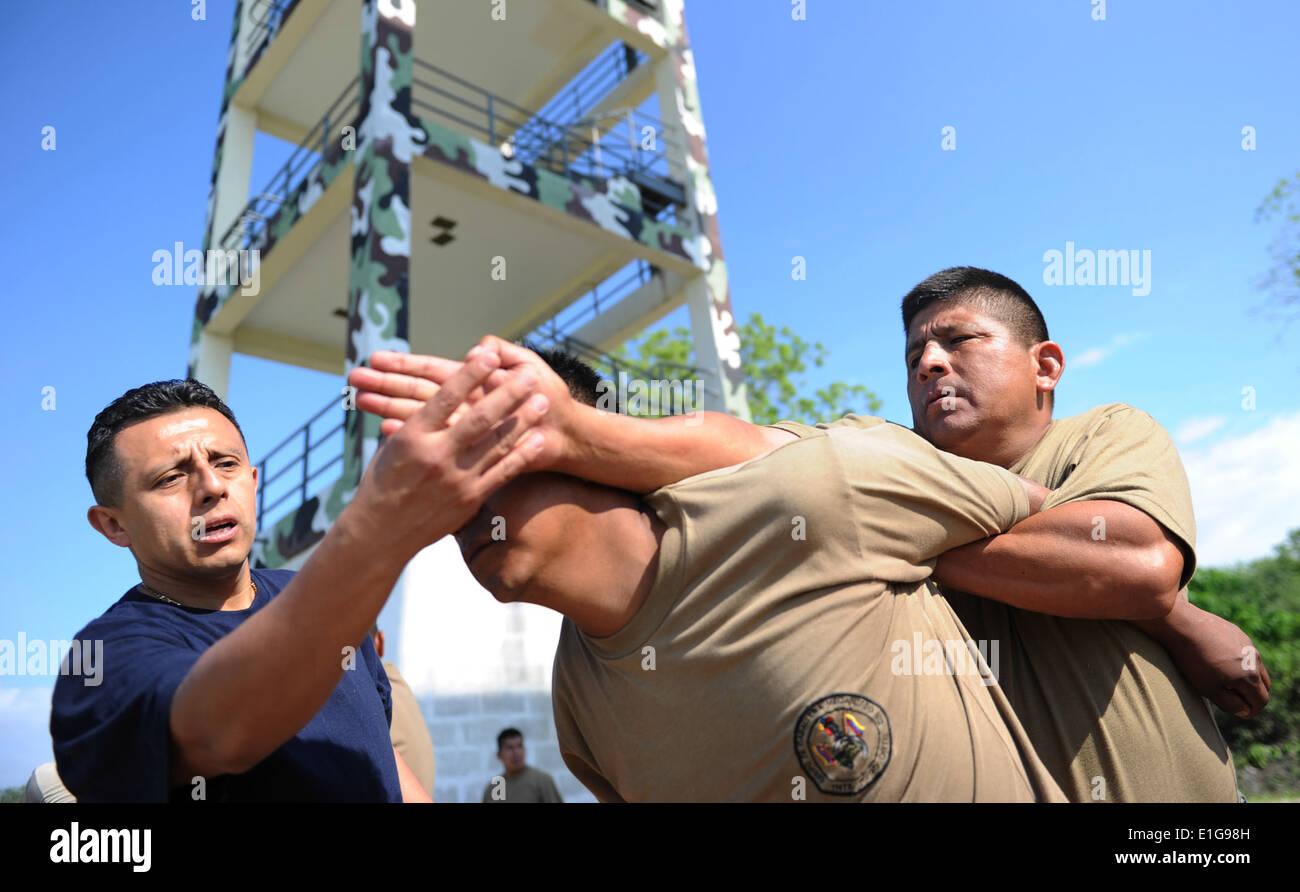 U.S. Navy Master-at-Arms 1st Class Luis B. Santana, left, adjusts an Ecuadorian soldier?s hands while teaching mechanical advan - Stock Image