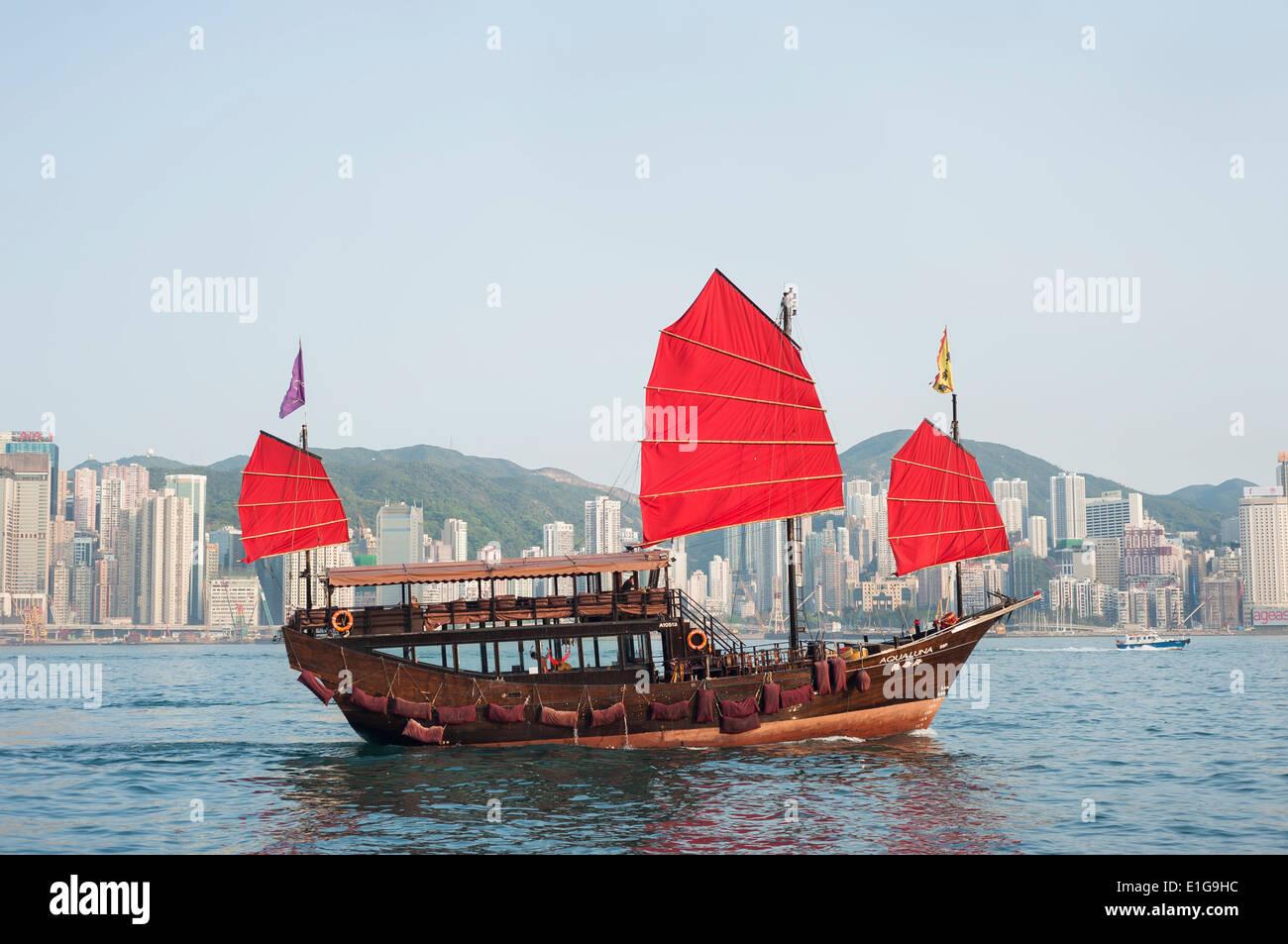 A tourist tour junk crosses Victoria Harbour, Hong Kong - Stock Image