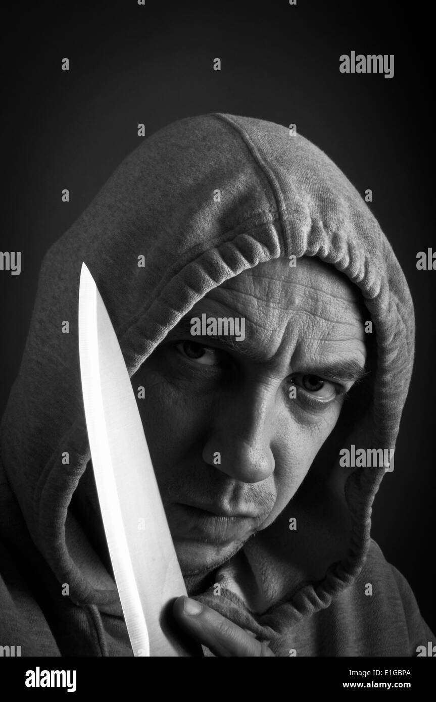 Hooded youth holding a knife Stock Photo