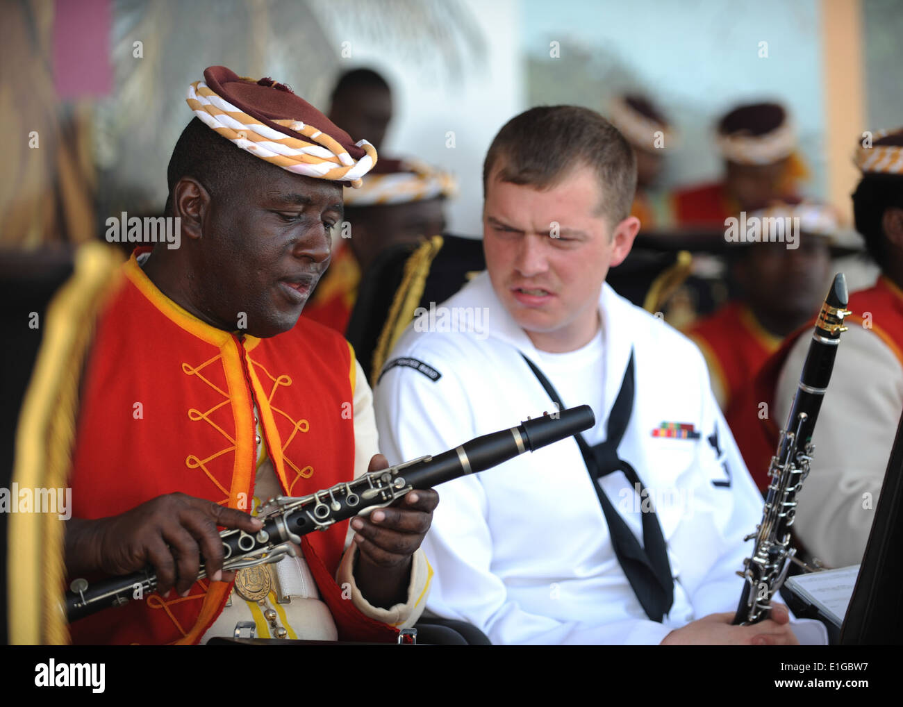 U.S. Fleet Forces Band member Navy Musician 3rd Class Fred Vaughan talks shop with a Jamaican Defense Force Band member during - Stock Image