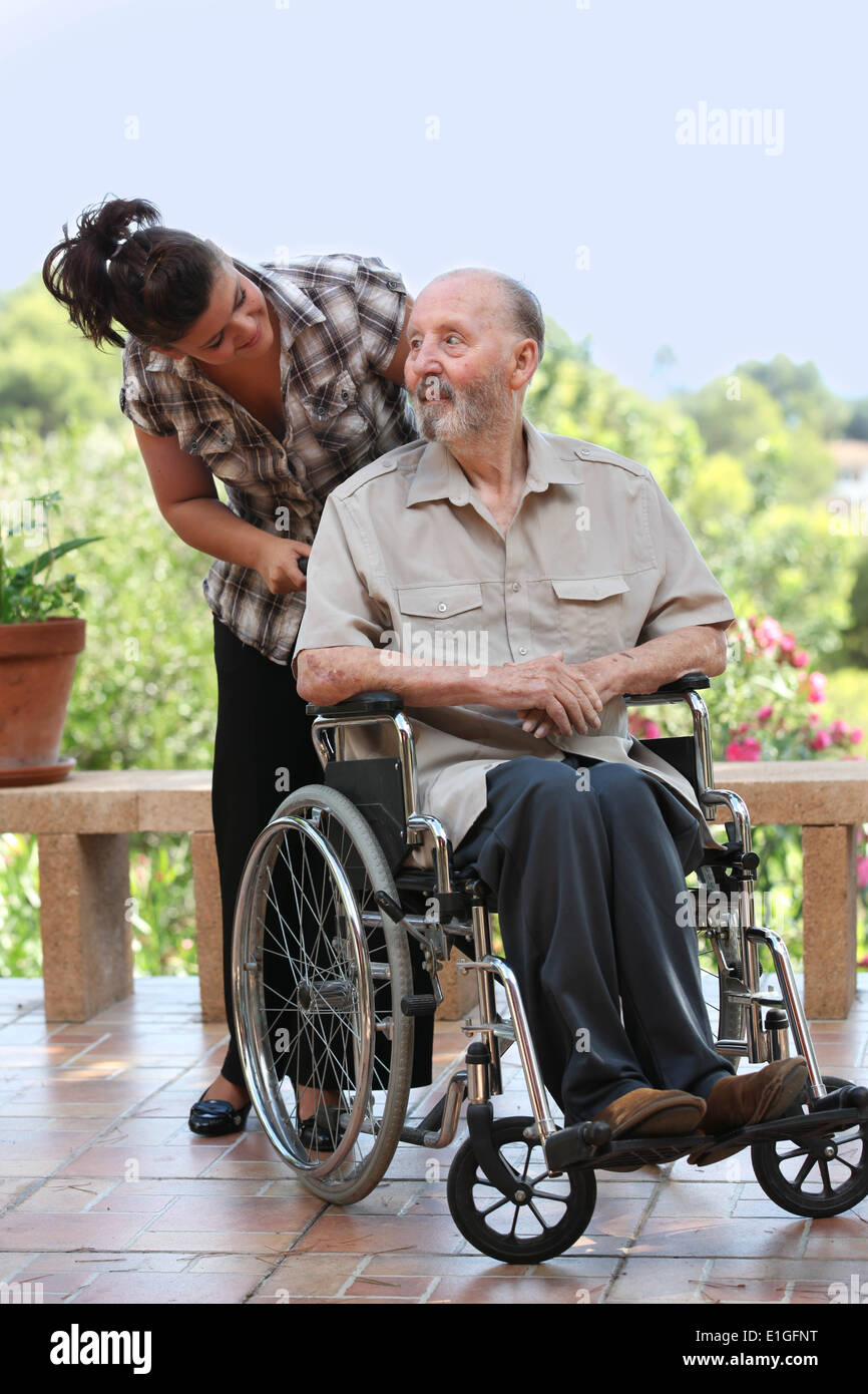 elderly man out for walk in wheelchair with grandchild - Stock Image