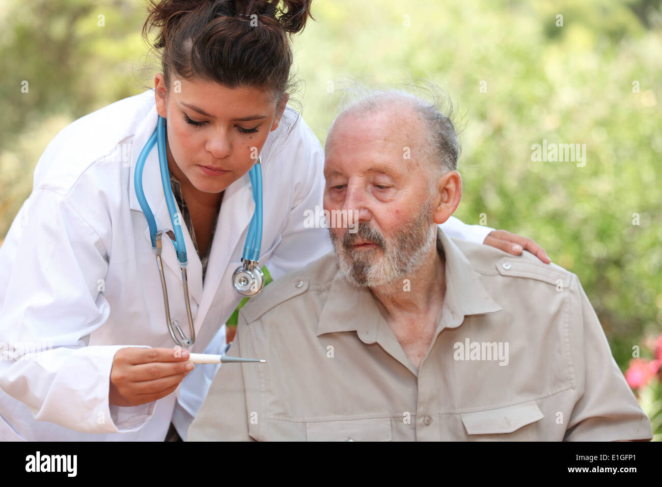 dr reading thermometer of senior man - Stock Image